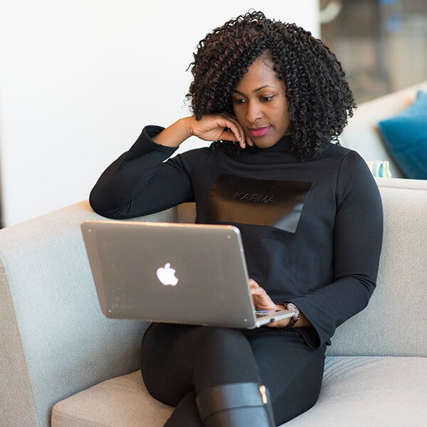 A woman sitting on a sofa while unloading forms using her laptop