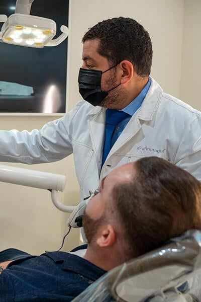 Dr. Almunajed working in the dental office with a patient in the chair