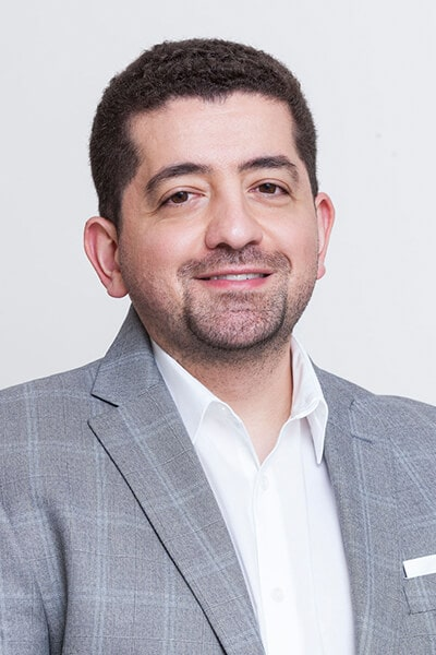 Dr. Husam Almunajed smiling in a gray suit