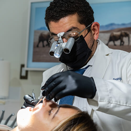 Dr. Husam checking the mouth of a young woman