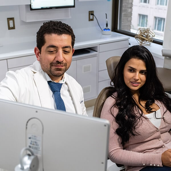 Dr. Husam Almunajed talking with a female patient in the Empire Dental office