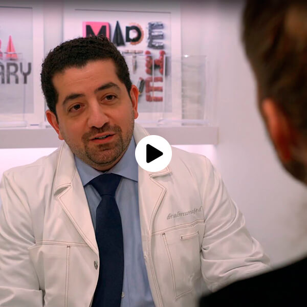 Dr. Husam Almunajed sitting talking to a patient